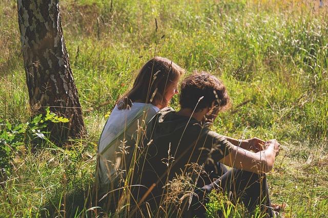Muž a žena spolu sedia v tráve.jpg