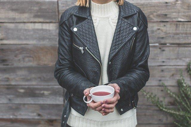 Žena v čiernej koženej bunde drží v rukách horúci čaj a stojí pri drevenej stene.jpg