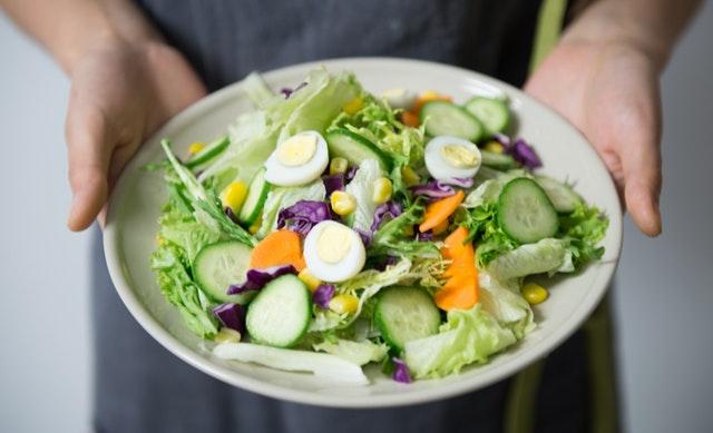 Človek drží v rukách zeleninový šalát s vajíčkom.jpg