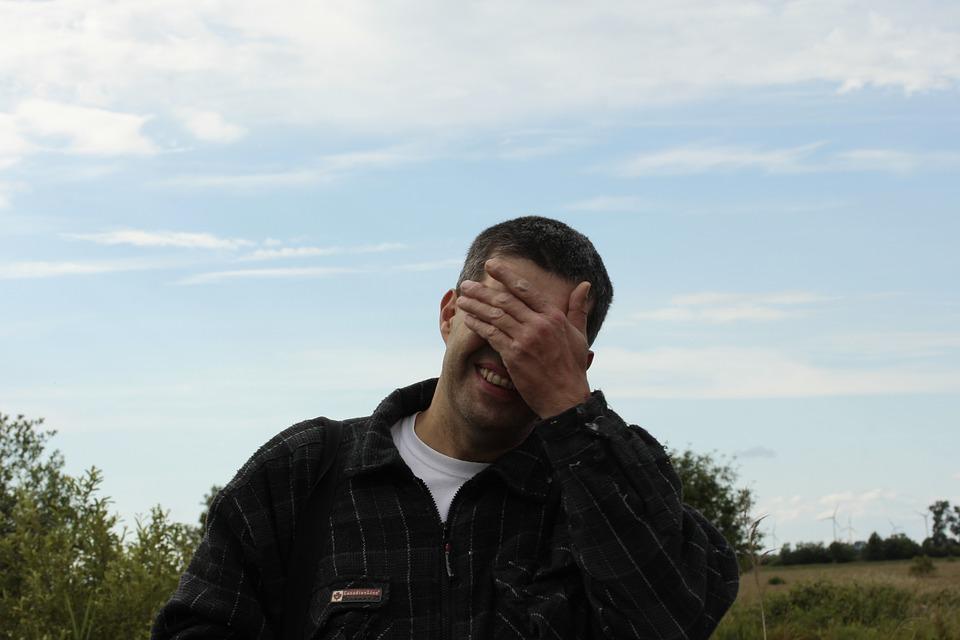 muž si zakrýva oči